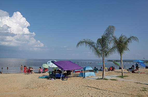 Beachgoers, colorful shelters and palm trees populate the smooth beach sands along the Potomac River in downtown Colonial Beach.