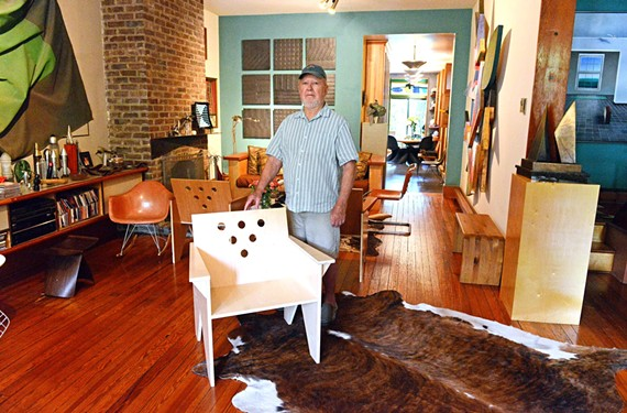 Harvey McWilliams stands by his plywood Harvey chair in his Fan District home.