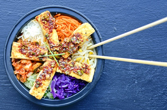 JKogi's tofu jorrim is a massive bowl of rice topped with grilled tofu and surrounded by carrots, cucumbers, pickled radish, kimchi, bean sprouts and purple cabbage.