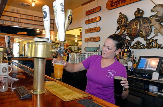 Bartender Courtney McKenna pours two drafts at the city's oldest craft brewery, Legend Brewing Co.
