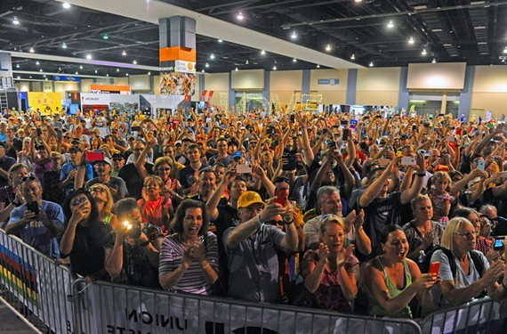 Inside the Greater Richmond Convention Center at the Fan Fest Zone, fans cheer for the USA cycling team's first-place victory in the elite men's time trial.