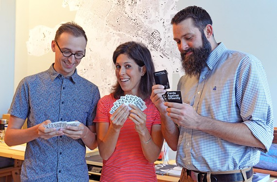Tyler King, Giles Harnsberger and Ryan Rinn check out cards from the Cards Against Urbanity RVA edition, which humorously take on the city's dysfunctions.