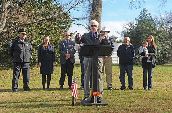 At a Byrd Park press conference, Glenwood W. Burley points to the spot where a Richmond police memorial statue will be relocated in 2016.