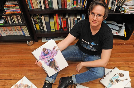 Jennifer Kennedy sits at home among her sketches of local musicians, including Dave Watkins in her hand.