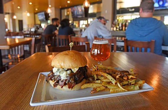 The bleu-bacon burger is a thick, hand-packed burger topped with gorgonzola,folded bacon and caramelized onions, paired here with a Shiplock IPA.