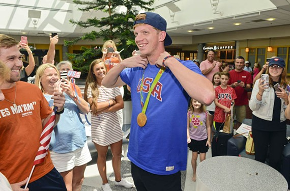 With his new gold medal around his neck, 19-year-old Richmond swimmer Townley Haas receives a warm welcome Monday, Aug. 15, upon his return from Brazil at Richmond International Airport.