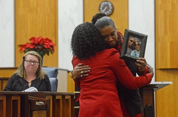 Angela holds a photo of her boyfriend Ronald Holder, who was murdered in October, at a memorial service in City Hall.
