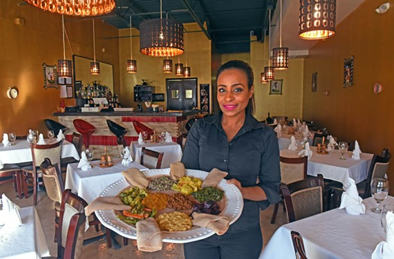 Owner Selam Belachew holds a vegetarian tasting platter that showcases some of Ethiopia's standout dishes, including gomen wat, kik alicha wat and azifa.