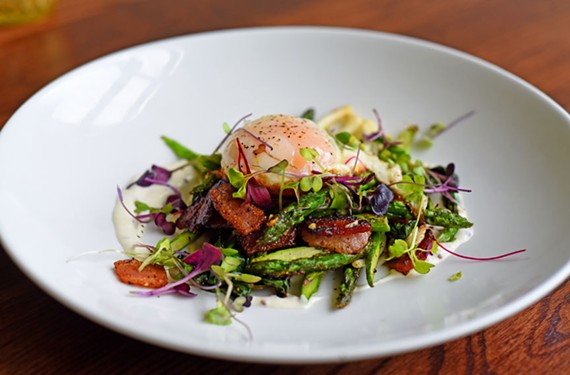 Chef Scott Lewis ribbons the warm asparagus salad with bacon, tops it with a fried egg and scatters the final dish with ramps, olive oil croutons and a drizzle of lemon dressing.