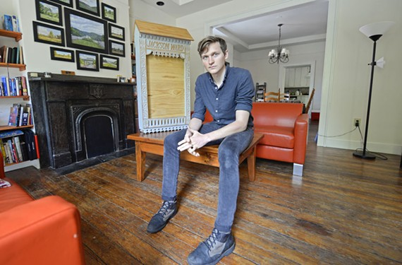 """Muralist and printmaker Barry O'Keefe sits inside his Jackson Ward home, near one of the sculptures he likes to call part of his """"wooden social network."""""""