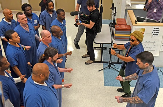 A film crew follows Speech, upper right, of Arrested Development, beside Garland Carr during a call-and-response session at the Richmond City Justice Center.