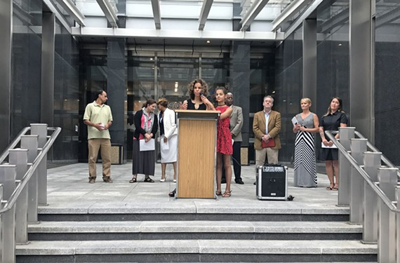Kenya Gibson's daughter holds the microphone as Gibson speaks at a news conference at City Hall on June 7. Ten advocacy groups called for the delay of the mayor's Education Compact.