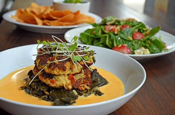 Crab cakes sitting atop greens are one dish on Vagabond's new, more approachable menu.