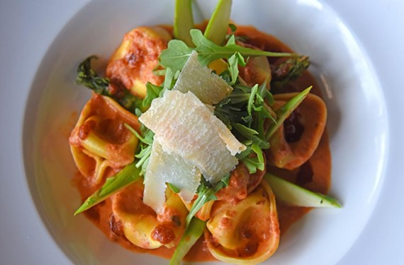 Cheese tortellini is surrounded by a pool of sundried tomato pesto cream and topped with asparagus and arugula.