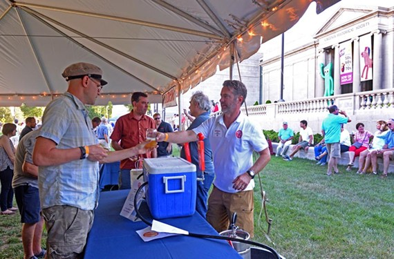 Kirk Candler, right, of Petersburg's Trapezium Brewing Co. serves a beer with ginger root on the front lawn of the Virginia Historical Society.