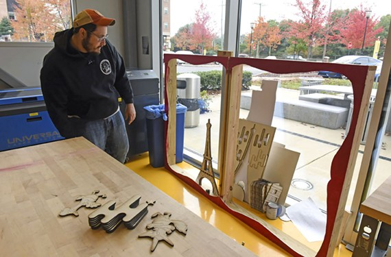 "Student Chad Hilton works on a Paris-themed storybook display for the window of 1z2z3z baby and toddler boutique on Patterson Avenue. ""The brand identity is Paris chic meets Southern sweet,"" he says, adding that he got to use his laser cutting skills."