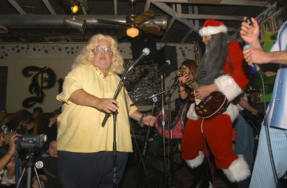 The dearly departed Donnie Corker, aka Dirtwoman, is shown here giving some mic love to guitarist and local reporter Mark Holmberg, during a Hamaganza charity event for FeedMore in 2004.