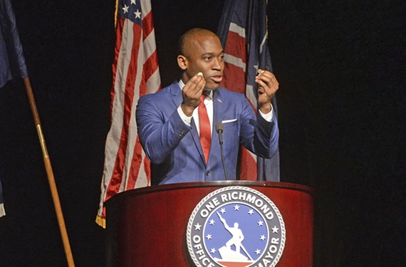 At the State of the City address, Mayor Levar Stoney holds up two pennies as props for illustrating his meals tax increase.