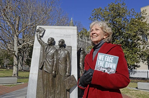 "Author Margaret Edds stands at the statue of civil rights lawyers Spottswood Robinson and Oliver Hill at Capital Square, holding her new book ""We Face the Dawn: Oliver Hill, Spottswood Robinson, and the Legal Team that Dismantled Jim Crow."""