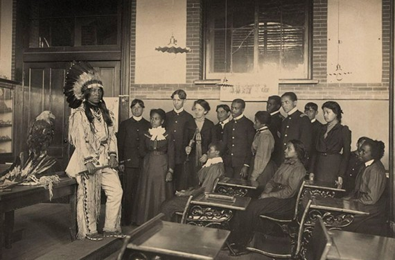 Louis Firetail, a member of the Sioux tribe, stands in full tribal clothing addressing an American history class. Between 1878 and 1923 more than a thousand Native Americans attended what is now Hampton University.
