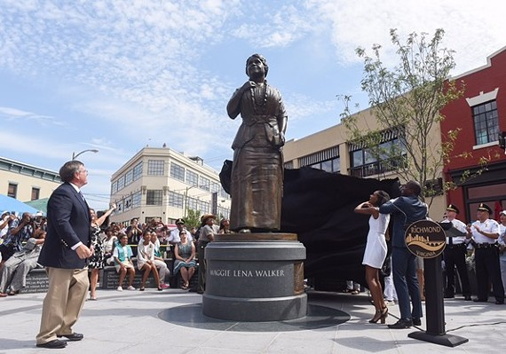 Sculptor Toby Mendez, left, watches Liza Mickens, the great-great granddaughter of Maggie Walker, and Mayor Levar Stoney pull a cover off the new statue to Walker.