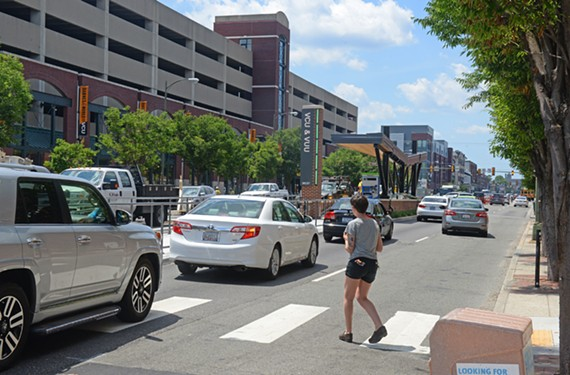 A pedestrian negotiates traffic on Broad Street near VCU at Laurel Street and a new Pulse stop.