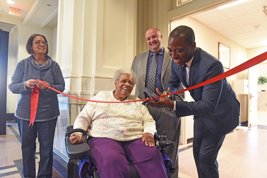 Mayor Levar Stoney, right, helps resident Kate Anthony cut a ribbon on a $5 million renovation of the 11-story William Byrd Senior Apartments. Anthony's daughter, Venecia Anthony, is at left, while Project: HOMES executive Lee Householder stands behind the mayor. - SCOTT ELMQUIST
