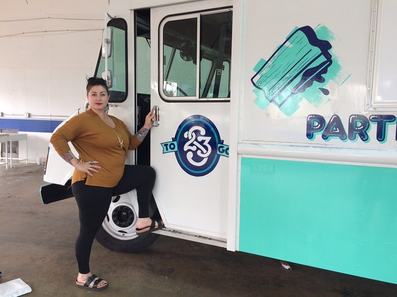 Recent Style Weekly Women in the Arts honoree, Ashley Hawkins stands next to Studio Two Three's new mobile studio.