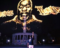 George Floyd's brother, Rodney Floyd, stands in front of the Jefferson Davis monument during a preview Monday night for the hologram of his sibling.