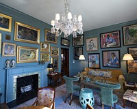 The living room decor of a penthouse at the Prestwould, a condominium built in 1927 on West Franklin Street, channels the 1930s with walls painted a shade of blue-green popular in the era and a carpet and chandelier from the decade.