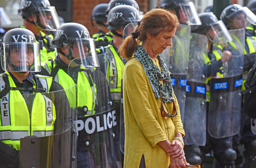 A protester turns her back on Virginia State Police, who had formed a barrier near Brooks Hall on the university›s grounds. - SCOTT ELMQUIST