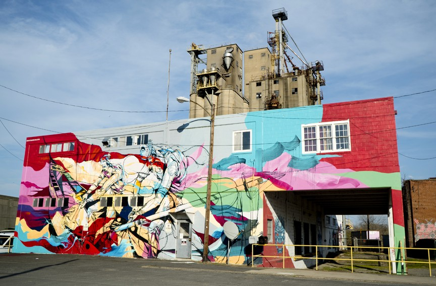 "Artist: Esteban del Valle (from New York); Location: Southern States Silos; In the book's interview, muralist Esteban del Valle says that he was thinking about the location's history in relationship to the slave trade. ""I chose to construct a fictional narrative where two slaves have managed to free themselves and have taken over their captor's ship. The red flag depicted is a reference to the red flags historically used to announce slave sales in progress … The masks were used as a way to re-imagine these figures as their own variation of an epic Greek myth."" - Broth notes that del Valle returned last year for the RVA Street Art Festival, painting young Puerto Rican baseball players over at the Diamond. - ""Esteban is just a really interesting guy,"" Broth says. ""His dad is a labor organizer who ran for mayor in Chicago against Rahm Emanuel. Lots of his work has political undertones, but at the same time they look cool."" - PHOTO COURTESY ""MURALS OF RICHMOND"""