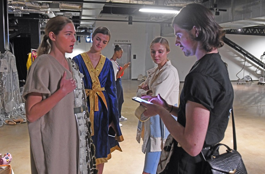 Backstage, sophomore Levi Haskins prepares the designs of another student for the trip down the runway. - SCOTT ELMQUIST