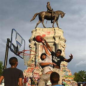 Melachi Cobbs attempts to dunk over his cousin Myles Bradley Cobbs at the Robert E. Lee monument on Juneteenth. The space has been unofficially renamed Marcus-David Peters Circle by Black Lives Matter protesters. - SCOTT ELMQUIST