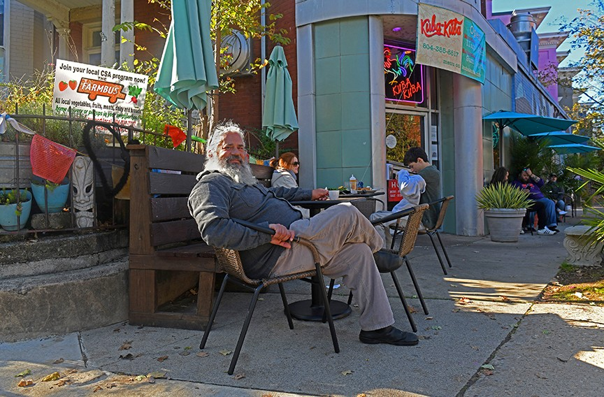 Chef and owner Manny Mendez sits outside of his 22-year-old Fan restaurant, Kuba Kuba, greeting passersby, and their pets, every morning. - SCOTT ELMQUIST
