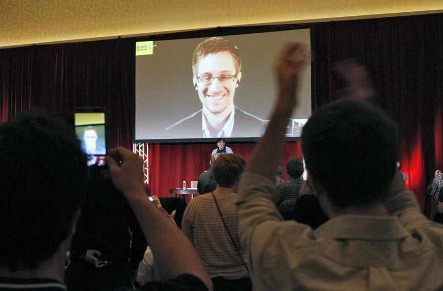 Supporters of Amnesty International cheer for accused government whistleblower Edward Snowden, who appears in a video feed during the 2014 Amnesty International Human Rights Conference in Chicago. WikiLeaks is a high-profile client of FitzGibbon Media. - REUTERS/FRANK POLICH
