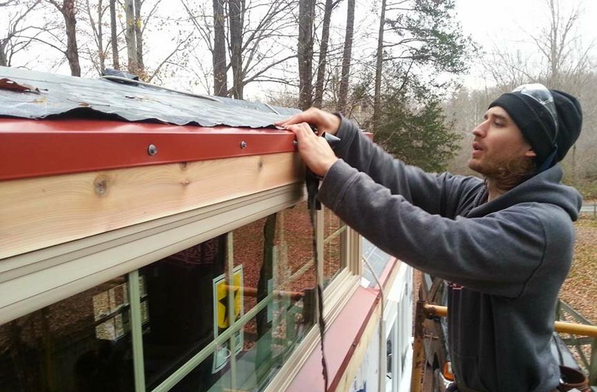 Numrich, who brought no construction experience to the project, works on the roof of his new house. He hopes to be moved in by the winter. - SCOTT ELMQUIST