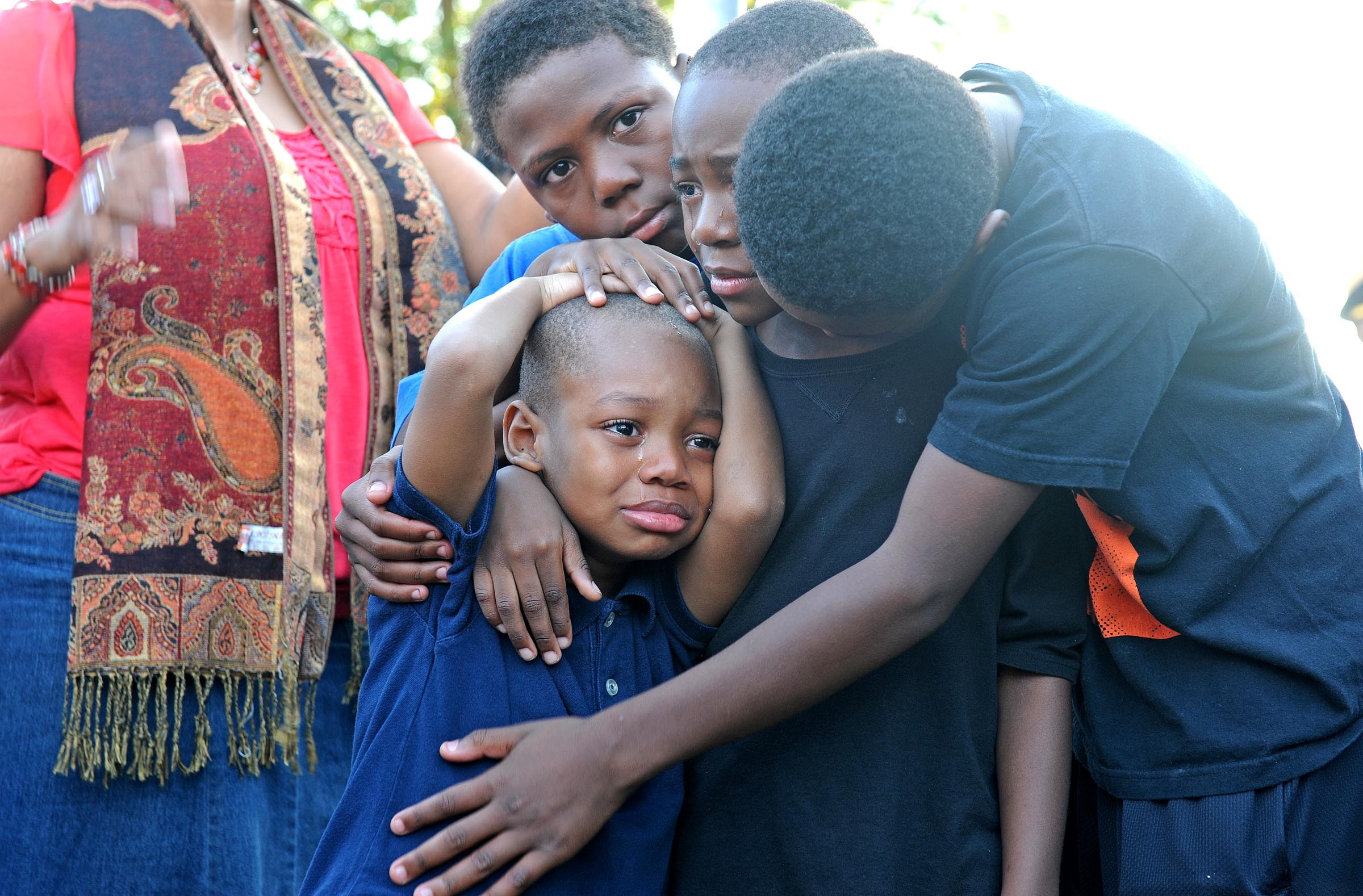Children comfort each other during a vigil mourning the death of William Crutchfield, whom police found dead in a Mosby Court residence in the early morning hours of Oct. 4, shot multiple times. Crutchfield's death is the ninth homicide in Richmond public housing this year. - SCOTT ELMQUIST
