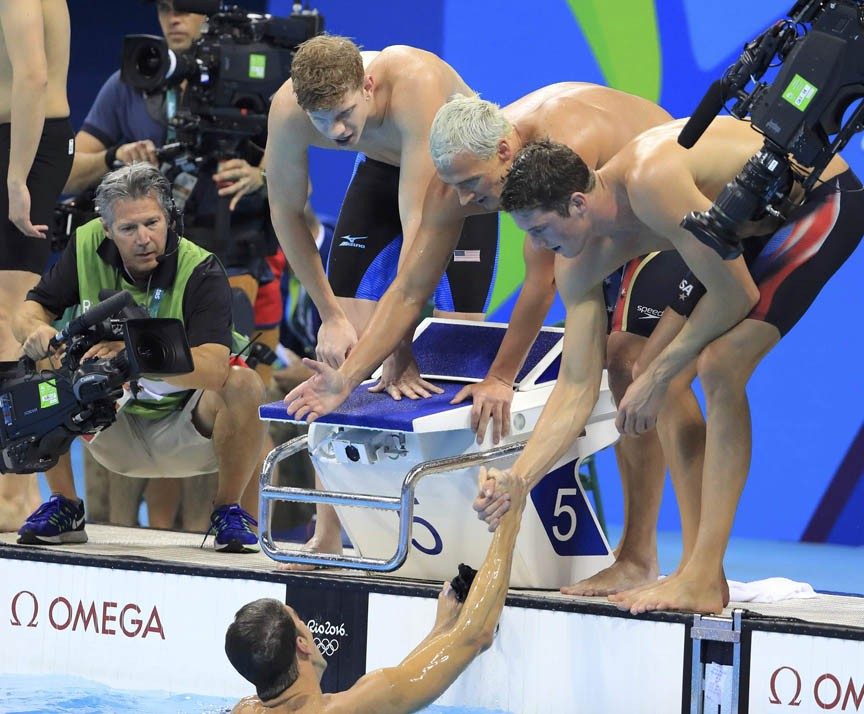 Townley Haas, Ryan Lochte and Conor Dwyer congratulate their teammate Michael Phelps after they win the gold medal in the men's 4x200-meter freestyle relay. - REUTERS/DOMINIC EBENBICHLER