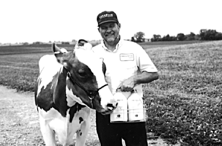 Ernie Wilson, a longtime home delivery driver who retired a few years ago, shows off one of the cows at an Oberweis farm.