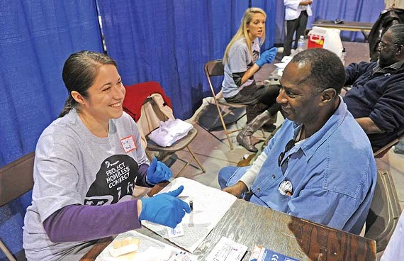 VCU pharmacy resident Toni Coe tests James Ragland for diabetes at the Nov. 17 Homeless  Connect event.