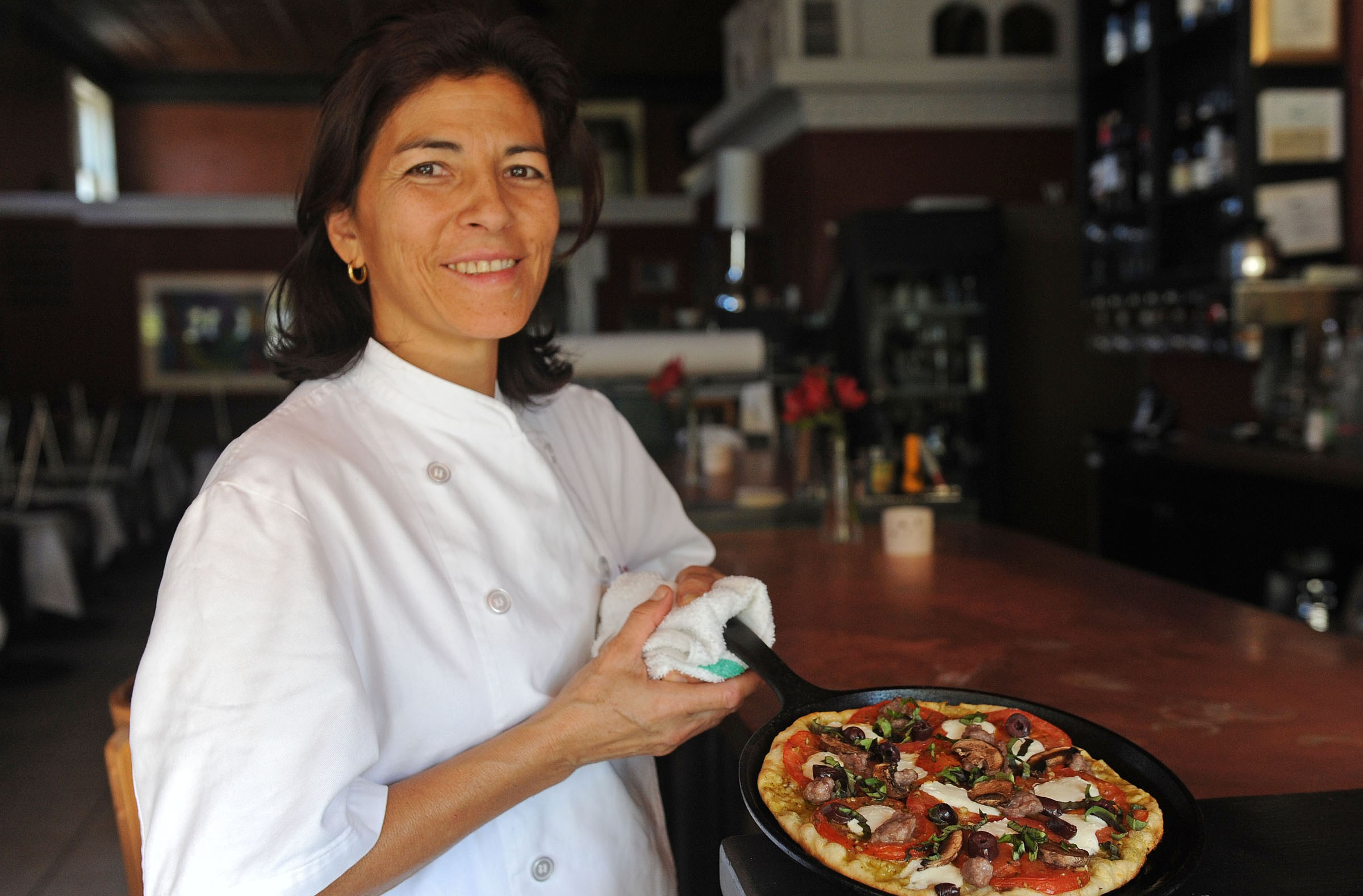 Virginia Rowland shows one of the skillet pizzas now on the menu at Rowland, which is changing its approach and prices. - SCOTT ELMQUIST