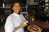 Virginia Rowland shows one of the skillet pizzas now on the menu at Rowland, which is changing its approach and prices.