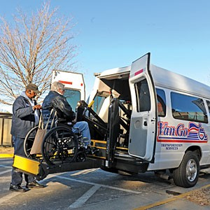 Walter Miles, a driver for Van Go Transportation Services, helps a wheelchair-bound patient into his van outside the Veteran Affairs Hospital in South Richmond. Photo by Scott Elmquist.