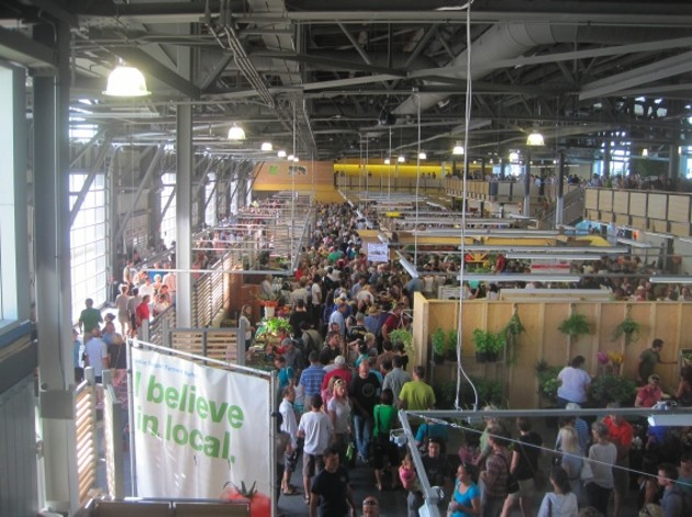 A bustling market scene, showing many people shopping at vendors.