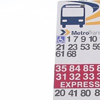 A current bus stop sign with many route numbers marked on it.