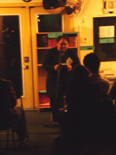 A fuzzy photo of Anna Quon reading.