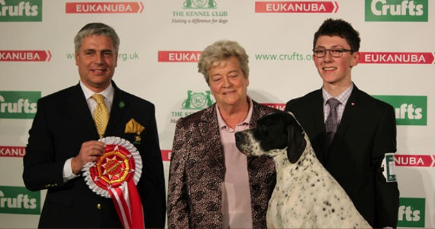 Colton O'Shea, at right, pictured with International Junior Handling Competition officials and English pointer Bob, gets his own ribbon for winning the world title.