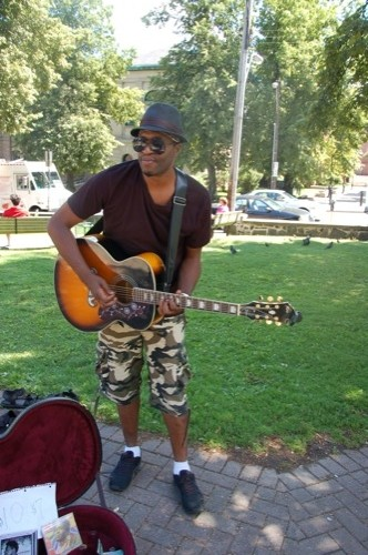"""Dammien, who had just finished a busking session at the Farmers' Market, looks for cool comfort when performing: """"I don't want to go down in leather,"""" he laughs. We like his new kicks, and the glimpse of the camouflage bandana peeking out from under his hat, which he recently bought in Toronto, when performing in Dundas Square."""