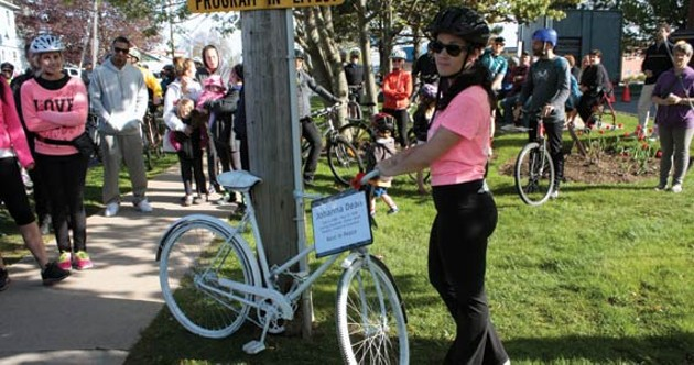 Julie Dean stands by her sister's ghost bike at a memorial rally in May